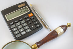 Calculator,Magnifying Glass, And Ballpoint Pen On White Background Royalty Free Stock Photos