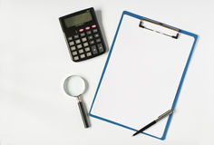 Calculator, magnifying glass and clipboard Stock Image