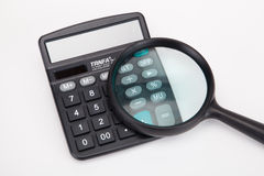 Calculator and a magnifying glass Royalty Free Stock Image