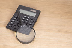 Calculator with magnifying glass lying on desk Royalty Free Stock Photography