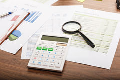 Calculator and magnifying glass on the table Royalty Free Stock Photos