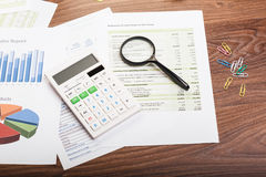 Calculator and magnifying glass on the table Stock Photo