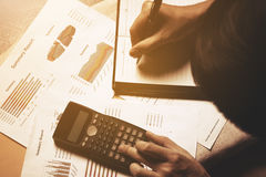 Calculator and man writing make note about cost. Royalty Free Stock Images