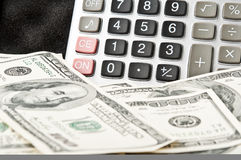 Calculator and many dollars Stock Photography