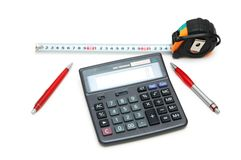 Calculator and measuring tape. Calculator, measuring  tape and pens isolated on white Royalty Free Stock Image