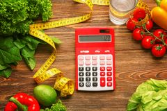 Calculator, measuring tape and set of healthy food. On wooden table Stock Photography