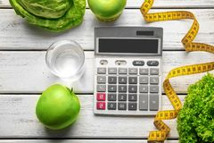 Calculator, measuring tape and set of healthy food. On wooden table Royalty Free Stock Image