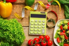 Calculator, measuring tape and set of healthy food. On wooden table Royalty Free Stock Photo