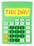 Calculator met BELASTINGSdag op vertoning op wit royalty-vrije stock fotografie