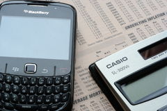 Calculator and mobile phone. Blackberry phone and casio calculator against finance news-page  black silver daylit Stock Photography