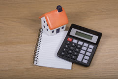 Calculator, model house and blank notepad Royalty Free Stock Photography