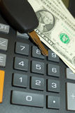 Calculator, momey and car key. Car key and money on keypad of a calculator close up Stock Images