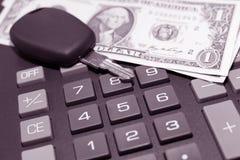 Calculator, momey and car key. Car key and money on keypad of a calculator close up Stock Image