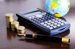 Calculator money coins with fountain pen and earth for loan mone Royalty Free Stock Images