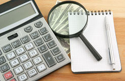Calculator, money, magnifying glass and notebook Stock Photos