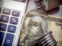 Calculator and money next to a light bulb, the concept of energy. Saving Stock Image