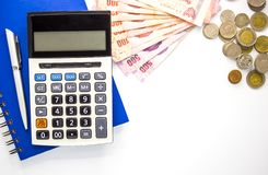 Calculator with money and Notebook on white background,top view,copy space stock photos