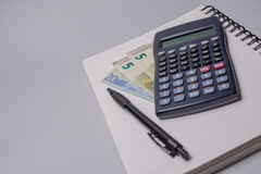 Calculator, money, pen and notebook on the office table on white background. Budget concept. Calculator, money, pen and notebook on the office table on white Royalty Free Stock Photo