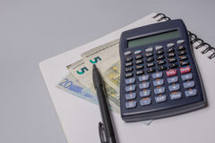 Calculator, money, pen and notebook on the office table on white background. Budget concept. Calculator, money, pen and notebook on the office table on white Stock Photos