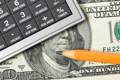 Calculator, money and pencil Stock Photography