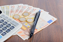 Calculator and money on the table Stock Images