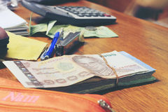 Calculator and money thai banknote with  white notebook paper, pen on wooden table at home office. The concept of financial planni Royalty Free Stock Photo
