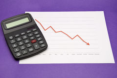 Calculator Next To Downtrend Chart. A calculator next to a generic downtrend chart Stock Image