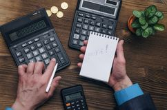Calculator. Note pad with copy space in businessman hands. Tax inspector or banker desk table background. Businessman male hands, notepad and calculator on Royalty Free Stock Photo