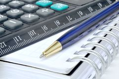 Calculator and notebook. Pocket calculator, notebook and blue pen Stock Image