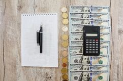 Calculator, notebook, dollars and coins. Hundred dollar bills and coins in a row on the table. View from above. stock images