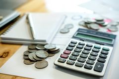 Calculator, notebook, pen, coins on his desk. To calculate income stock images