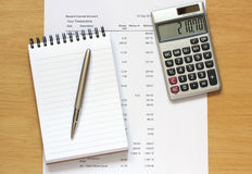 Calculator notebook pen and financial figures Stock Photography