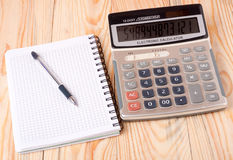 Calculator with notebook and pen on a light wooden table Stock Photos