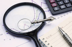 Calculator, notebook, pen, magnifier and financial chart, busine Stock Photography