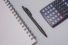 Calculator, notebook and pen on the office table on white background. Budget concept. Calculator, notebook and pen on the office table on white background Royalty Free Stock Photography