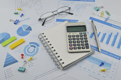 Calculator, notebook, pen, pin and glasses on financial graph, a Stock Photo