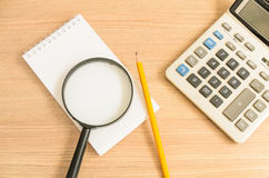 Calculator and notebook and pencil and glass Royalty Free Stock Photos