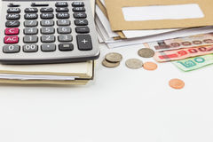 Calculator on notebook, pile of mail, coins and bank notes on white background. Royalty Free Stock Image