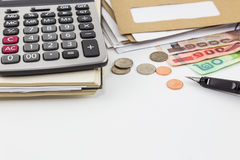 Calculator on notebook, pile of mail, coins and bank notes on white background. Royalty Free Stock Images