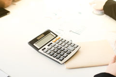 Calculator, notebook and some documents on white conference tabl Royalty Free Stock Photo