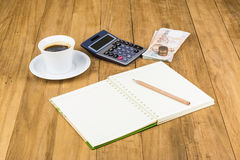 Calculator and notebook on wooden table Stock Photos