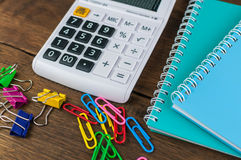 Calculator, notebooks & clips on wooden background Stock Image