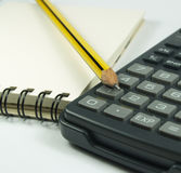 Calculator and notepad. A composition of one black and yellow pencil one white notepad and one calculator royalty free stock photo