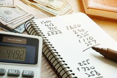 Calculator and notepad with calculations after counting money. Stock Images