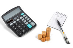 Calculator and notepad with coins Stock Photo