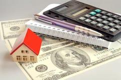 Calculator, notepad and a hundred dollar. Pocket calculator, notepad, pen and a small house on a hundred dollar bill Royalty Free Stock Photos