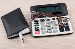 Calculator, notepad, pen and glasses on table Stock Photography