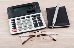 Calculator, notepad, pen and glasses on table Stock Photos