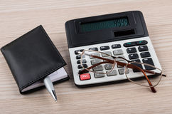 Calculator, notepad, pen and glasses on table stock images