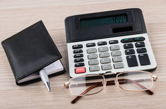 Calculator, notepad, pen and glasses on table Royalty Free Stock Photos